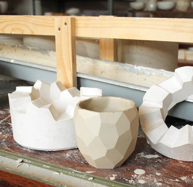The poligon cup in front of the two piece mold that is used for casting